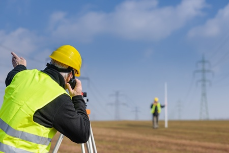 Land surveyors measuring with tacheometer speaking through transmitter construction site