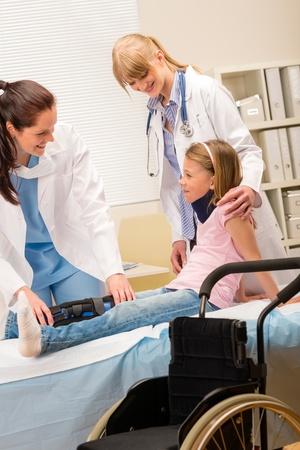 Two female doctors examine broken leg little girl wheelchair