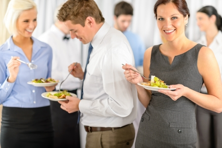 Photo pour Smiling business woman during company lunch buffet hold salad plate - image libre de droit