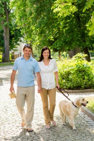 Couple in love walking Labrador dog in park sunny day