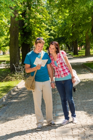 Young couple looking at map in park happy tourists holiday