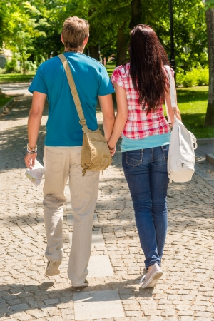 Couple holding hands walking in the park from behind love