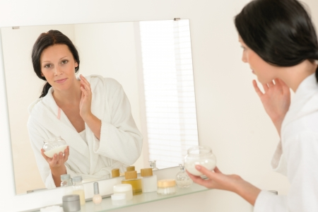 Woman looking in bathroom mirror and applying face moisturizer cream