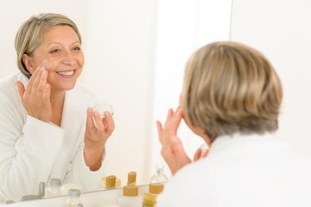 Senior woman looking in bathroom mirror and applying anti-wrinkles cream