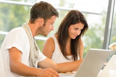 Photo pour High-school pupils using laptop for school project academic library smiling - image libre de droit