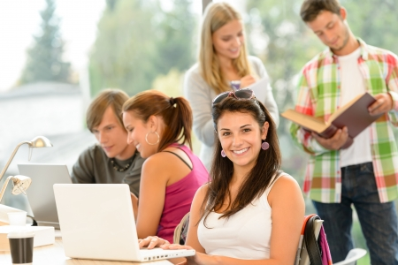 Teens studying in high-school library young pupils smiling laptop book