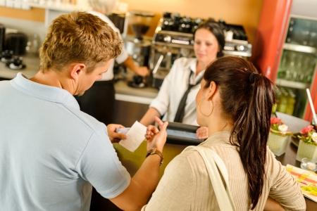 Man checking receipt at cafe restaurant payment waitress couple bar