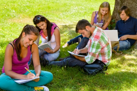 Students sitting in park studying reading writing teens campus schoolyard