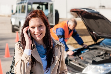 Woman talking on cellphone after car breakdown trouble problem mechanic