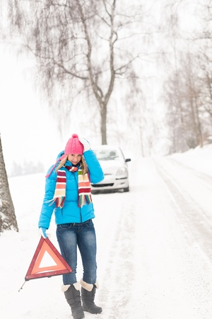 Woman with reflector triangle car snow breakdown problem winter traffic