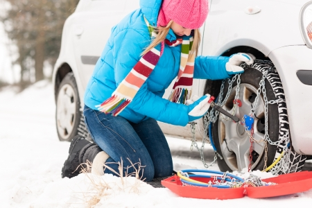 Woman putting chains on car tires snow broken winter fixing