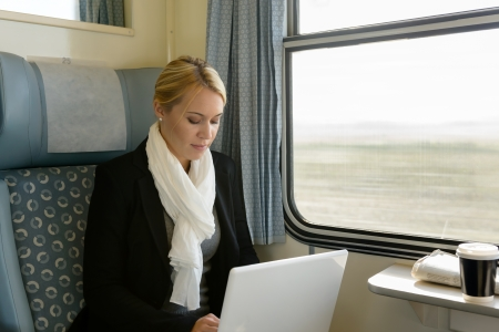 Woman using laptop traveling by train commuter serious technology reading