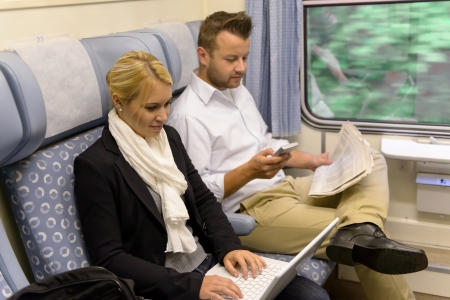 Woman with laptop man newspaper in train texting commuting reading