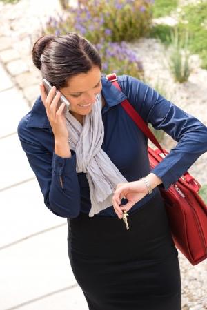 Woman calling rushing arriving home keys smart phone elegance business