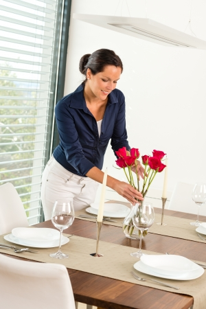 Young woman placing flowers dinner table romantic