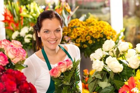 Photo pour Smiling florist flower shop colorful making bouquet roses market - image libre de droit