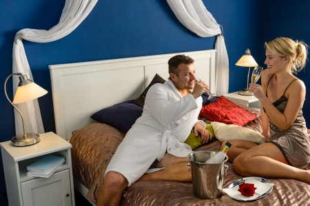 Romantic hotel room young couple sexy nightgown robe drinking champagne