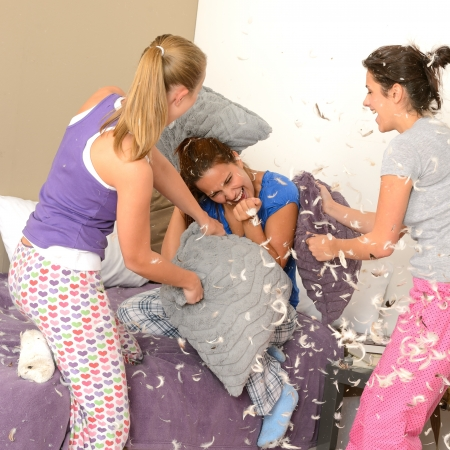 Teenager girls pillow fighting in bedroom with flying feathers