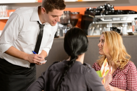 Waiter taking orders from young woman customer in restaurant