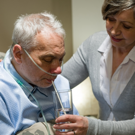 Nurse helping senior sick man with drinking glass of water