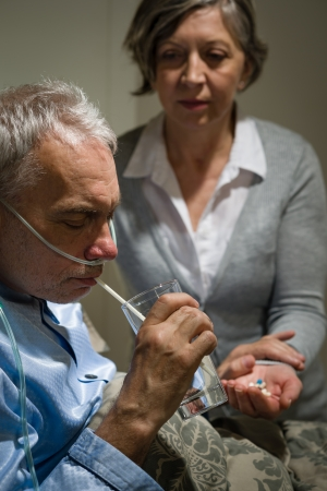 Caring senior wife holding drugs for her sick husband