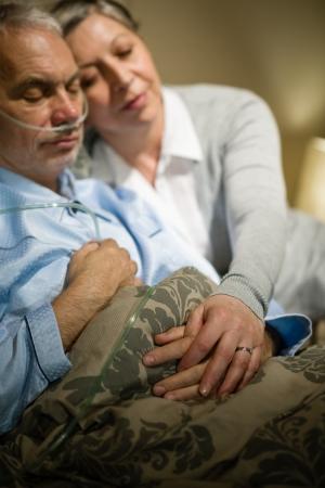 Loving elderly couple sleeping in bed sick husband