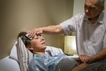 Caring senior man helping his sick wife lying in bed
