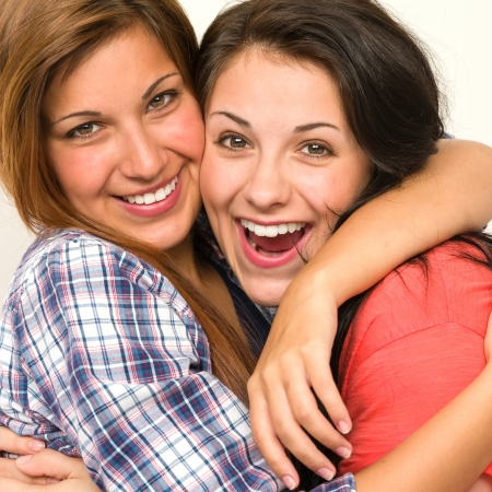 Caucasian sisters friends embracing and  laughing at camera