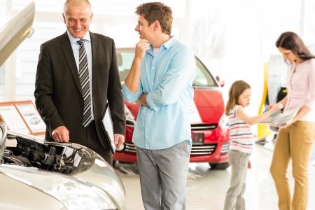 Photo pour Car salesman showing the engine of the car - image libre de droit