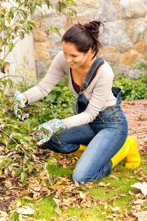Happy woman gardening clippers backyard autumn hobby pruning kneeling