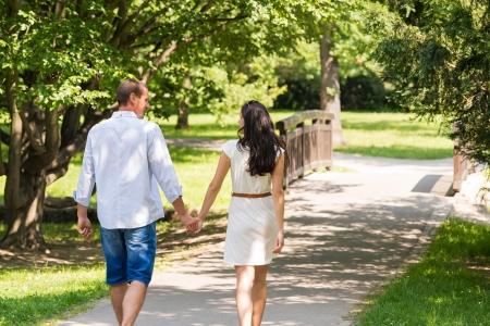 Rear view of walking caucasian couple in park