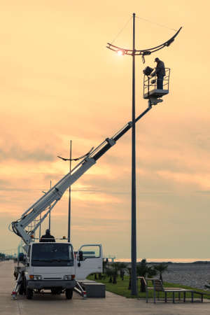Photo pour Profession repair and maintenance of street lamps - car with crane lifted an electrician to replace bulbs at sunset in evening. Toned in style filters. Empty copy space for text. - image libre de droit