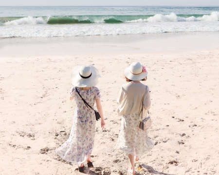 Rear view of two young women in long dresses and hats walking along sandy beach meet sea water. Bali island. Concept of wonderful holiday, escape from city bustle, female friendship.
