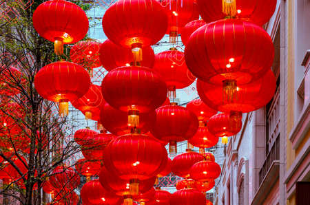 Photo pour Rows of Chinese lanterns in an alley between buildings - image libre de droit