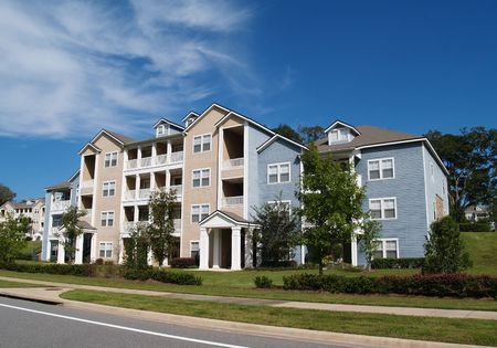 Three story condos, apartments or townhomes with vinyl siding of blue and tan.