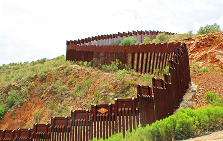 Photo pour Border Fence beside a road near Nogales, Arizona separating the United States from Mexico. - image libre de droit