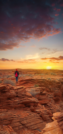 girl standing in the Grand Canyon watching the sunset alone.