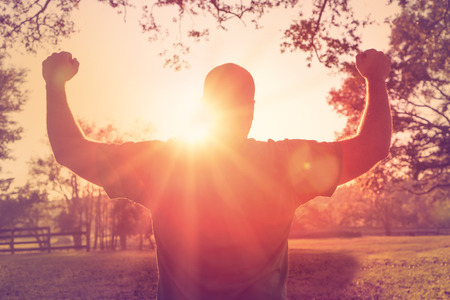 Foto de Successful happy accomplished man stands with raised arms facing the sun. White male athlete with arms up celebrating and happy with his acheivement and exercise. - Imagen libre de derechos