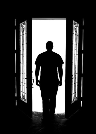 Silhouette of man in doorway with windows with arms at sides looking out while mysterious solitary meditative reflective lonely thoughtful patient dangerous serious imagining