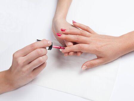 Photo pour Closeup shot of woman`s hands in a nail salon receiving a manicure on a white background - image libre de droit