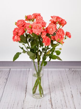 Photo pour Beautiful bouquet of red roses in transparent glass vase. On white  grey background - image libre de droit