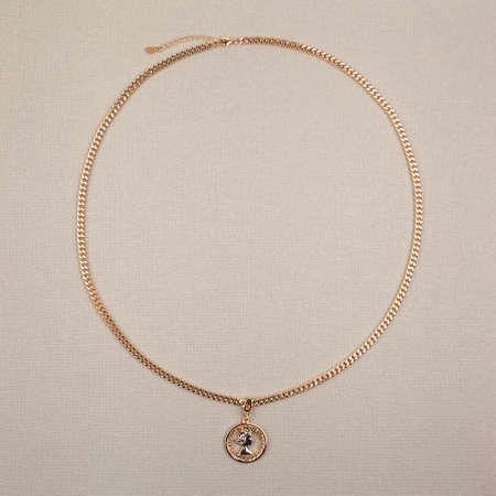 Photo pour Female golden pendant with chain on beige textured background. Close-up shot - image libre de droit