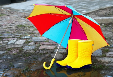Pair of yellow rubber boots with an open umbrella beside a puddle