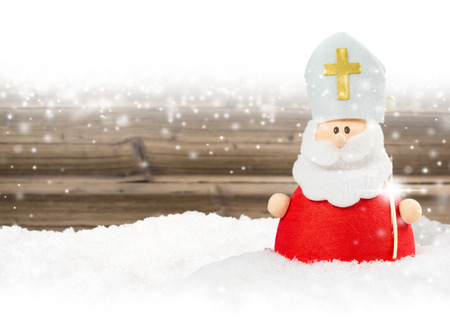 Photo of Saint Nicolas on wooden board background with falling snow and white space