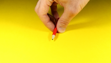 Hand placing a red pencil on a yellow sheet