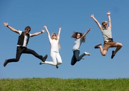 Group of young people jump across blue sky