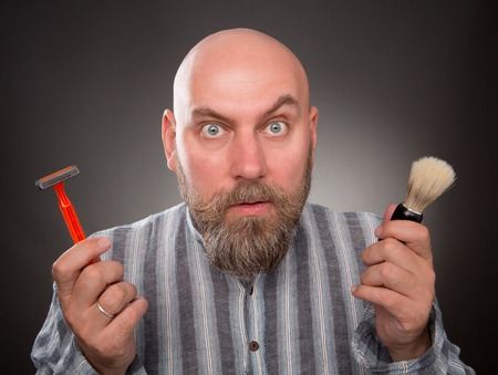 Astonished jailbird posing with razor and brush in his hands. Bold bearded man is very surprised isolated on dark grey.