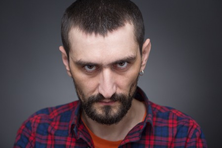 Hipster bearded man looking defiantly at photographer. Man with black short hair in plaid shirt is very angry or serious.