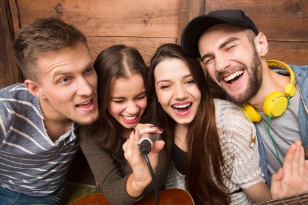 Two men and two ladies spending their free time in karaoke. Modern people singing songs and happy smiling for the camera.