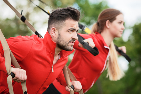 Closeup portrait of sport man and woman training in park with suspension trainer sling. Handsome man looking in front of him.